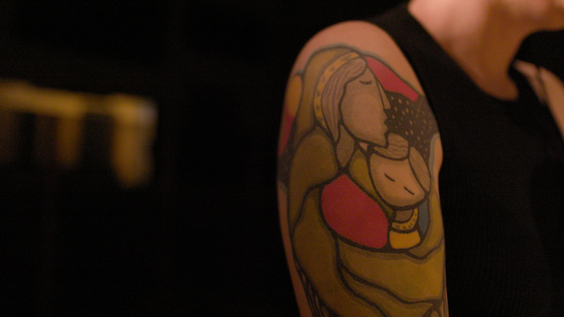 arm tattoo of mother embracing infant